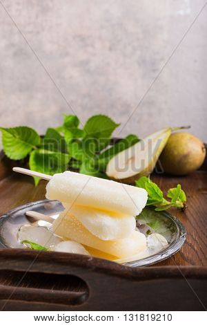 Homemade pear popsicles on metal plate with ice and pears. Summer food concept. With copy space.