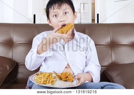 Picture of a little boy enjoying fried chicken and french fries while sitting on the sofa at home