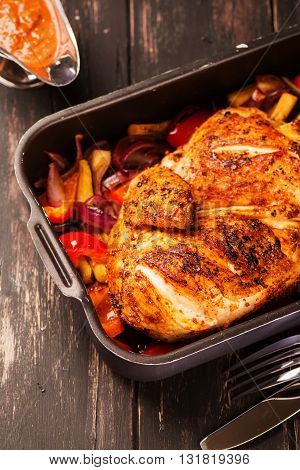 Grilled chicken with baked vegetables and spicy sauce on black table
