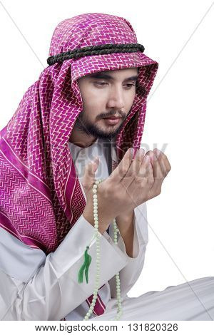 Portrait of a young middle eastern man wearing headscarf while holding beads and praying