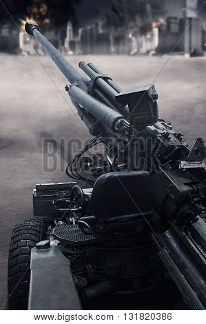 Image of a military cannon shooting in the battle at the city shot outdoors