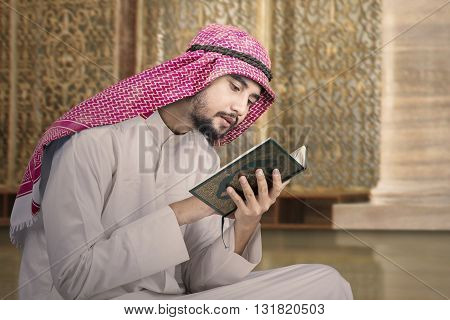 Portrait of a young middle eastern person sitting in the mosque while reading Quran