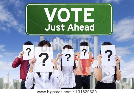 Image of unknown people covering face with question mark near the board with vote text