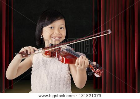 Portrait of a beautiful little girl smiling at the camera while playing a violin on the stage