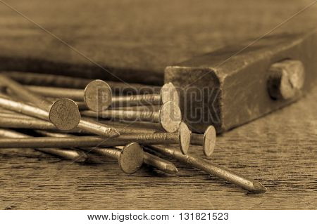 Vintage old hammer with rusty nails on wood table background