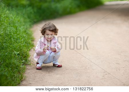 little girl on the road and sees a flower