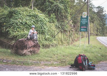 Backpacker waiting for hitchhike on the road for Kubah National Park West Sarawak Borneo Malaysia. People traveling lifestyle. Desaturated and toned image instagram style.