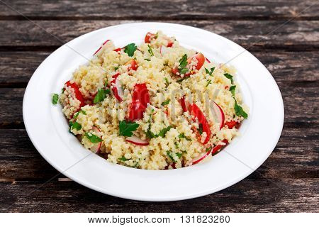 Homemade Fresh Couscous salad with vegetables, in white plate