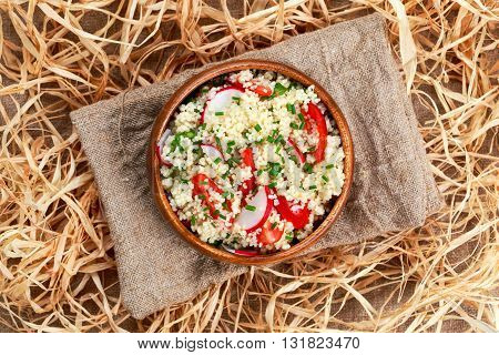 Homemade Fresh Couscous salad with vegetables wooden bowl on straw