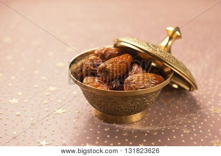 Ripened dates in a metal bowl. An important fruit in middle east. A golden bowl of dates.