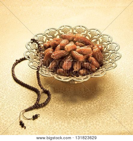 Tropical date fruits in an ornamental golden bowl with Islamic prayer beads. Ramadan