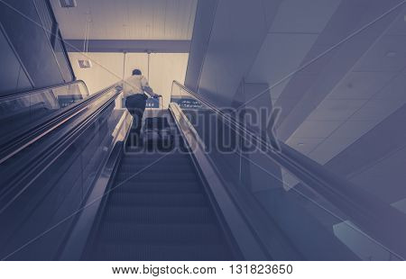 Business man with luggage taking escalator to the top floor.  Business travel concept image