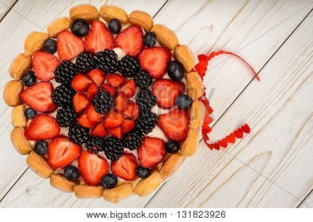 Biscuit cake with strawberries, blueberries and blackberries on white wooden background.