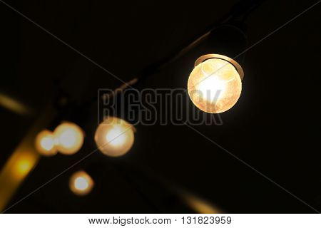 decorating hanging bulbs light in  dark place.  small luminous light bulbs hanging in dim place.