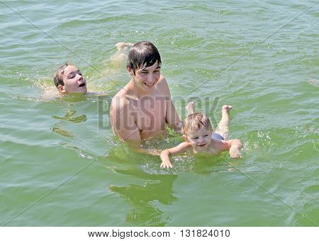 Three Happy Boys bathing in the Water