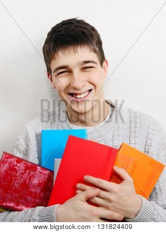 Cheerful Teenager with a Books by the White Wall