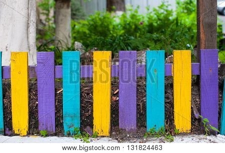 Decorative multicolored wooden fence near the house.