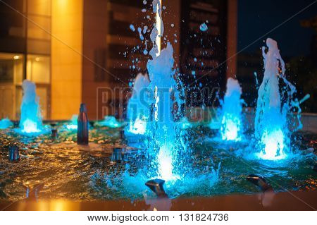 blue illuminated fountains in the night city.