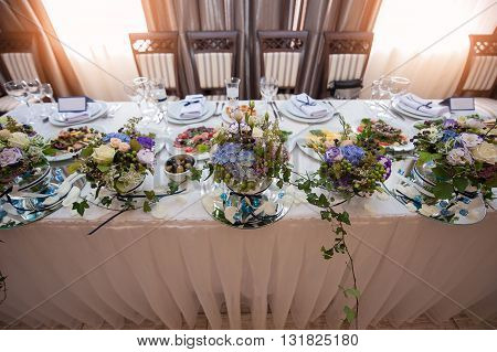 beautiful decor of flowers on a wedding table in a restaurant.