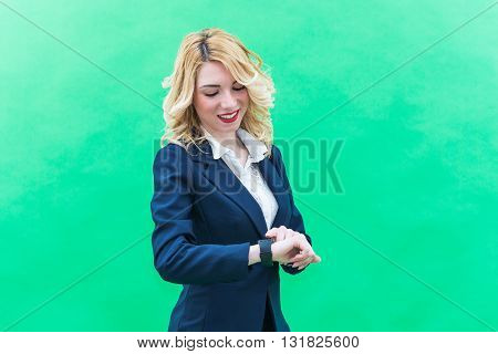 Young woman using smartwacth standing. Wearing blue suit she has blonde hair and blue or blue eyes on a white background. Smile always smiling.