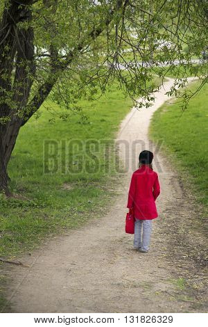 small girl in red raincoat go away by winding pathway