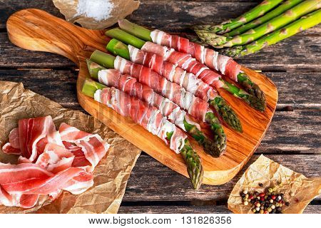 Fresh Organic raw Bacon Wrapped Asparagus on wooden table