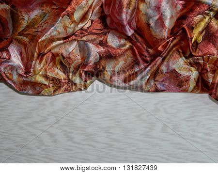 on a wooden Board is silk with abstract figures in brown tones