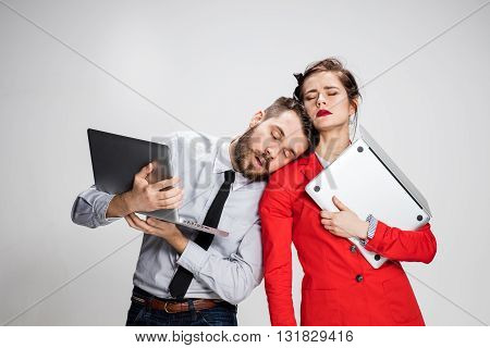 The yawning and bored sleeping young businessman and businesswoman with laptops on gray background. The concept of relationship of colleagues.