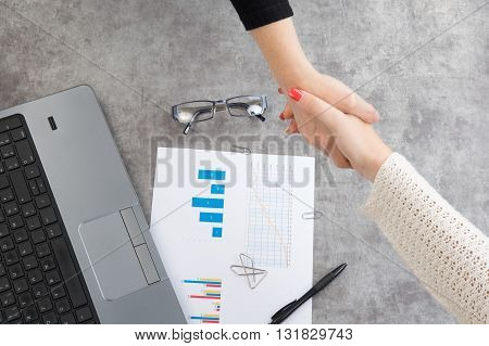 Two Business people shaking hands indoorsat office