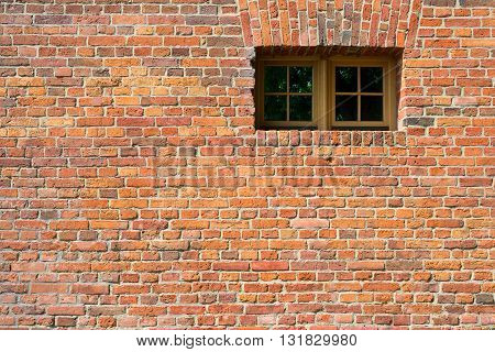 Small modern plastic window on vintage old brick wall background. Glass isolated with patch