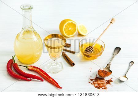 Home red pepper tincture in a glass and fresh lemons on the white wooden background in rustic style, selective focus