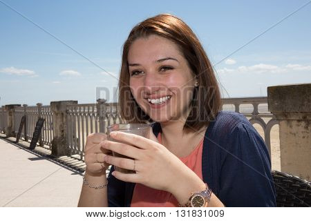 Smiling Woman Sitting On Beach With Cup Of Hot Beverage