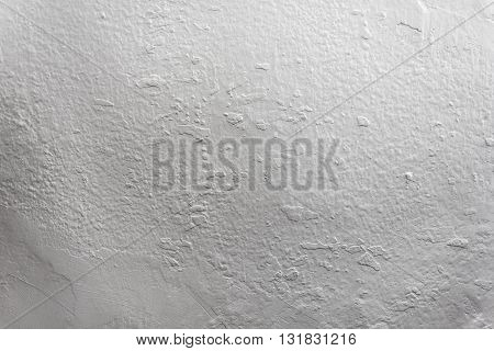 Irregular grainy texture of a painted white wall.