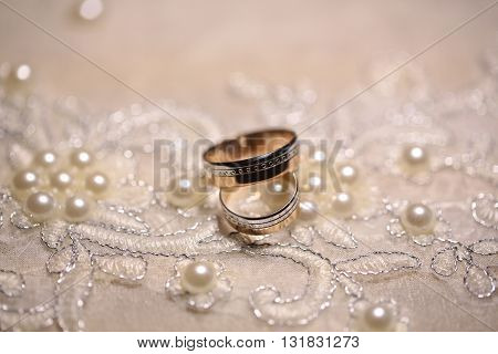 Wedding bands on white cloth richly embroidered with pearls on blurred background