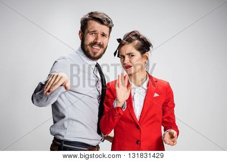 The funny business man and woman rejecting anything on a gray background. Business concept of relationship of colleagues