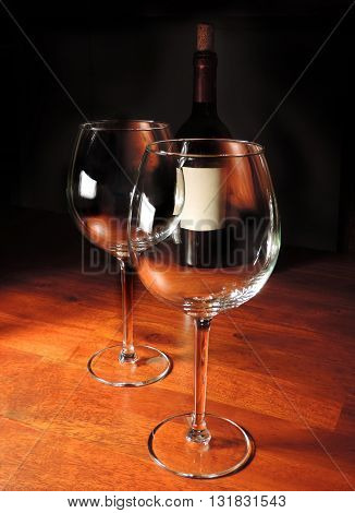 two wine glasses and bottle on a wooden table, black background