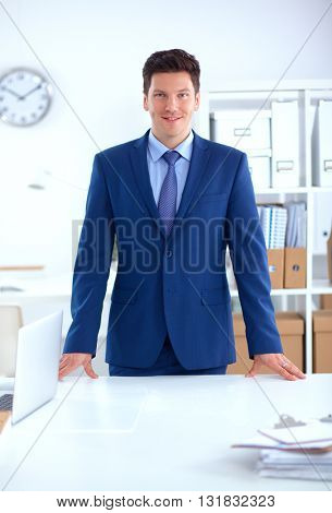 Business man or manager standing against his desk at the office