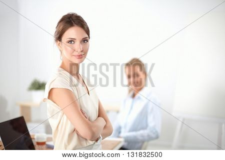 Attractive businesswoman standing near wall in office