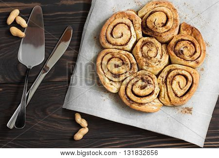 Buns with cinnamon on a wooden background knife and blade