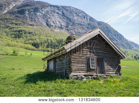 Norwegian mountain cabins of wood with grassy rooftops surrounded by stunning nature..