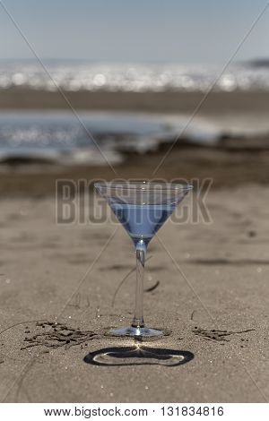 Glass With Water On The Sandy Beach