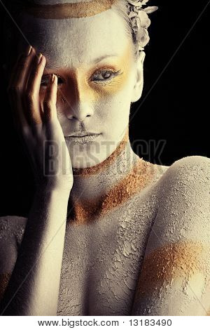 Portrait of an artistic woman painted with white and bronze colors, over black background. Body painting project.