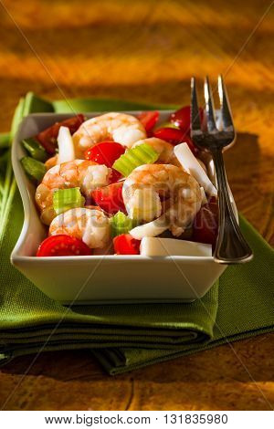 Shrimp salad with squid tomatoes celery inside a white bowl