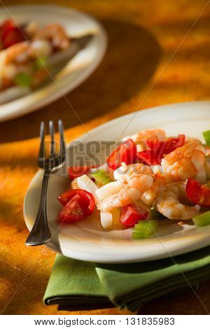 Shrimp salad with squid tomatoes and celery over a green napkin with an orange background