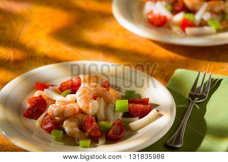 Shrimp salad with squid tomatoes and celery over an orange background