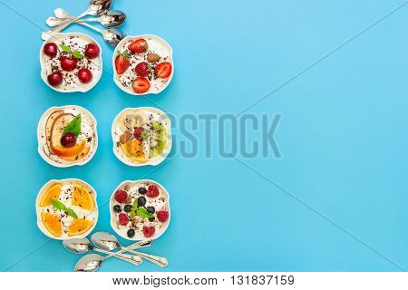 Left 6 different yogurts displayed vertically in 2 rows of 3 pieces near spoons right empty space on light blue background. Six yogurts and empty space. Horizontal. Top view.