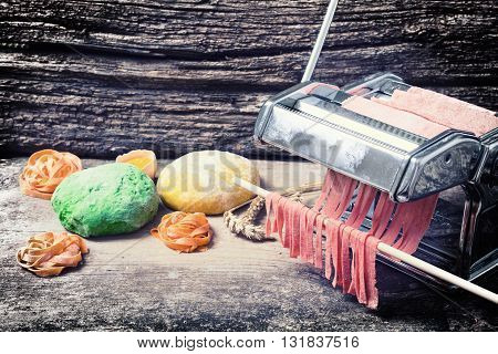 Preparation of homemade pasta on wooden background