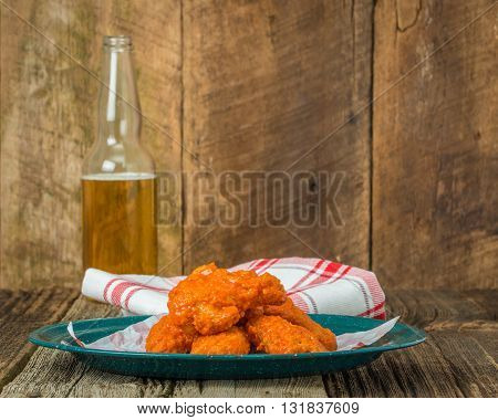 Spicy buffalo style chicken wings on a tin plate.