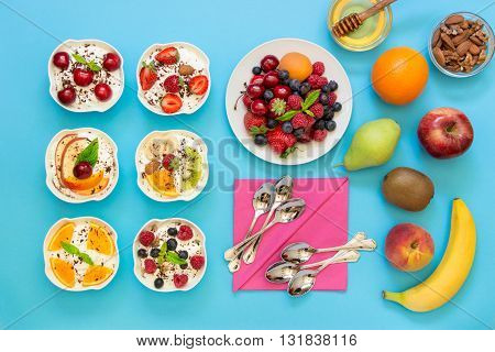 6 bowls of differently dressed yogurts displayed vertically in 2 rows near plate of berries fruits nuts honey 6 spoons napkins on blue background. Six different yogurts and ingredients. Top view.