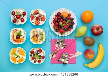 6 bowls of differently dressed yogurts displayed vertically in 2 rows of 3 pc. near plate of berries fruits 6 spoons napkins on blue background. Six yogurts ready to eat and ingredients. Top view.